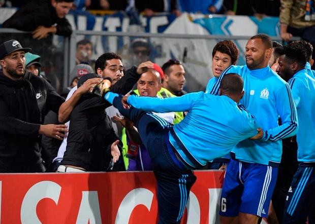 Patrice Evra kicks out at a Marseille fan prior to last night's Europa League game against Vitoria in Portugal
