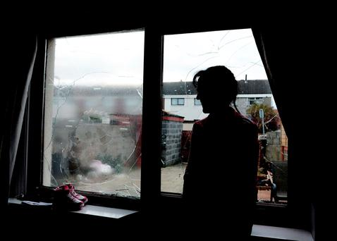 Mother at her home with smashed windows. Photo: Caroline Quinn
