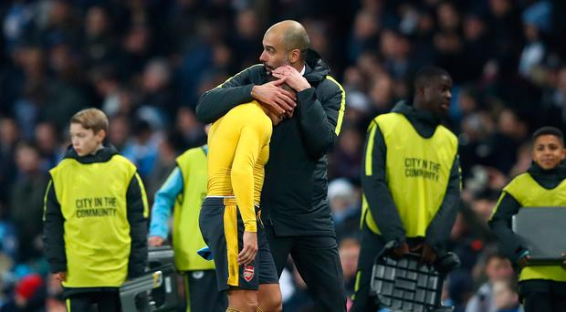 Alexis Sanchez of Arsenal (L) and Josep Guardiola, Manager of Manchester City (R) embrace after the final whistle during the Premier League match between Manchester City and Arsenal at the Etihad Stadium on December 18, 2016 in Manchester, England. (Photo by Clive Brunskill/Getty Images)