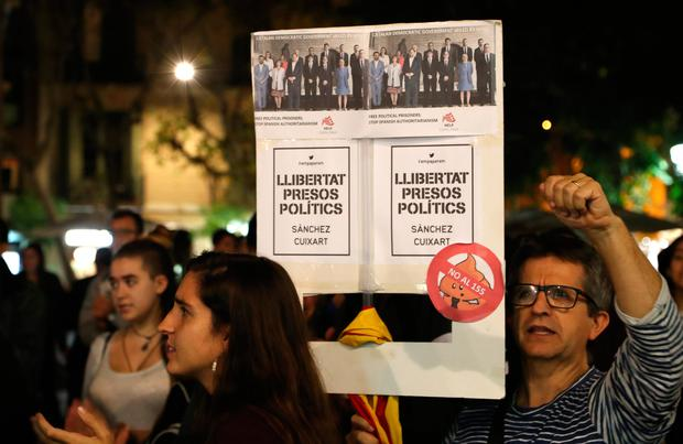 A protester holds aloft a placard calling for the release of political prisoners in Barcelona. Photo: Getty Images