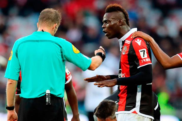 Nice's Italian forward Mario Balotelli (R) reacts after receiving a red card by French referee Olivier Thual (L), during the French L1 football match between and Dijon on November 5, 2017 at the Allianz Riviera stadium in Nice, southeastern France. / AFP PHOTO / VALERY HACHEVALERY HACHE/AFP/Getty Images