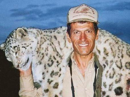 Hossein Golabchi smiles with the big cat draped over his shoulders, which appears to have been shot twice in its hind leg