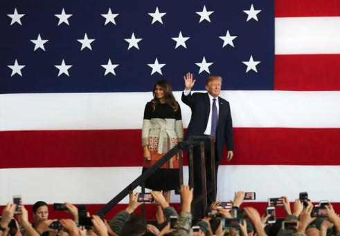 U.S. President Donald Trump, right, with first lady Melania Trump, waves to the U.S. troops at the U.S. Yokota Air Base, on the outskirts of Tokyo