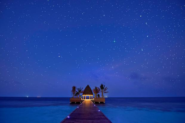 A canopy of stars dot the night sky above the arrival jetty at Kandolhu Island