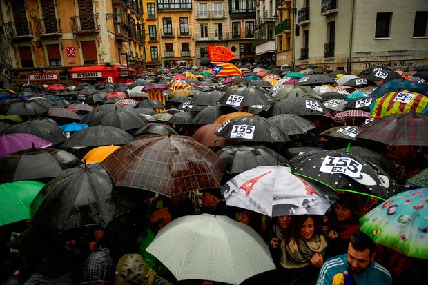 People in Pamplona, northern Spain, take shelter under umbrellas during a protest against Madrid's power grab. Photo: AP