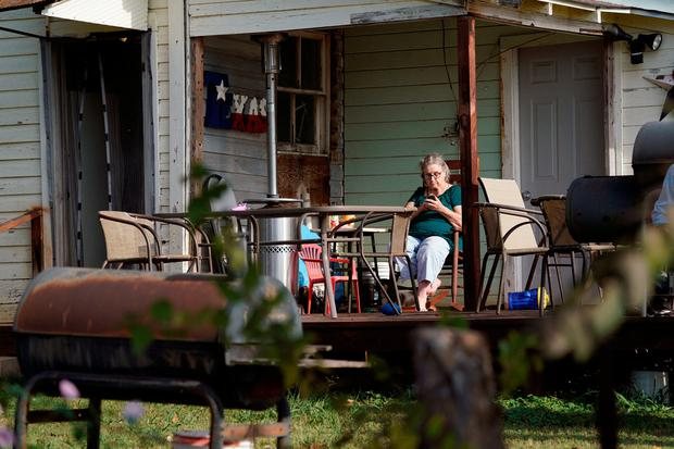A woman looks at her phone, on her porch next to the site of a shooting at the First Baptist Church of Sutherland Springs, Texas, U.S. November 6, 2017. REUTERS/Rick Wilking