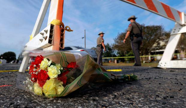 A bouquet of flowers lies at the base of a roadblock where law enforcement officials work at the scene of a shooting at the First Baptist Church of Sutherland Springs, Monday, Nov. 6, 2017, in Sutherland Springs, Texas. . (AP Photo/Eric Gay)