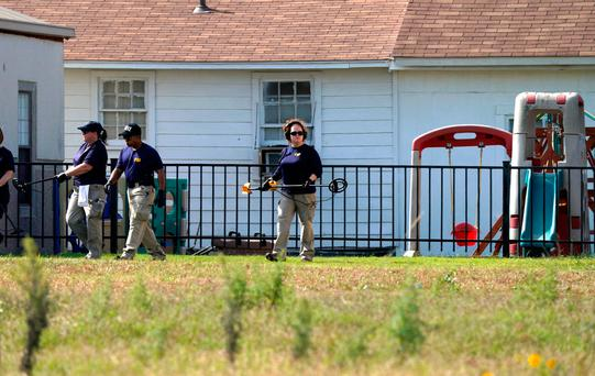 Members of the FBI Evidence Response Team use metal detectors at the playground at the site of the shooting at the First Baptist Church of Sutherland, Texas, U.S., November 6, 2017. REUTERS/Rick Wilking