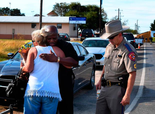 Local resident Jamie Rose is hugged by church member Raymond Antonio as she delivers flowers to the First Baptist Church in Sutherland Springs, Texas. Photo: AFP/Getty Images