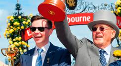 Joseph O'Brien and owner Lloyd Williams pose with Melbourne cup after Rekindling won