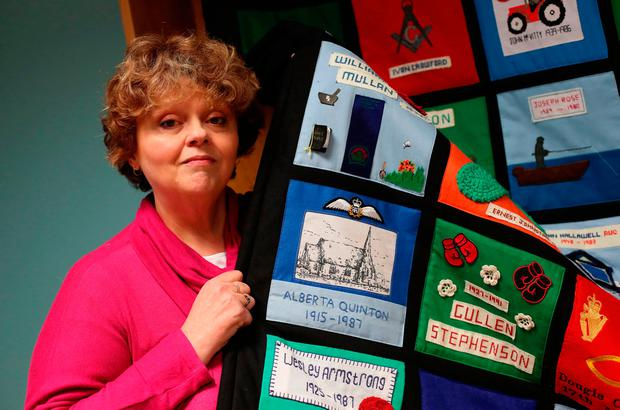 Aileen Quinton, whose mother Alberta Quinton was murdered in the Enniskillen bombing, holds a quilt she helped make as a memorial Niall Carson/PA Wire