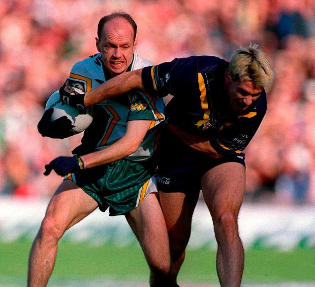 Peter Canavan tangles with Jason Akermanis during the 2000 series. Photo: Brendan Moran/Sportsfile