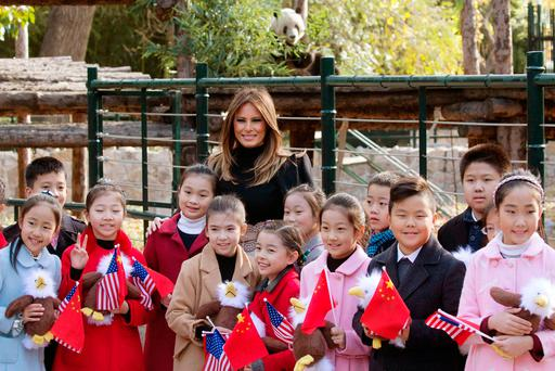 U.S. first lady Melania Trump poses for photos with Chinese children holding flags and the bald eagle dolls near the panda enclosure at a zoo in Beijing, China, Friday, Nov. 10, 2017. . (AP Photo/Ng Han Guan)
