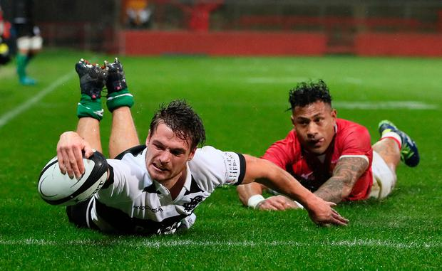 Barbarians' George Bridge goes over for his side's second try despite pressure from Tonga's Takalua Sonatane. Photo: PA Wire