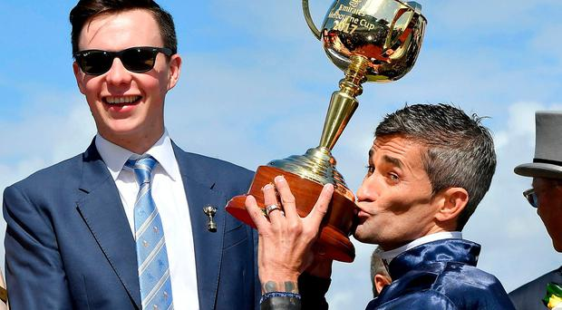 Jockey Corey Brown, right kisses the winning trophy for media in the mounting yard watched on by trainer Joseph O'Brien. Photo: Andy Brownbill/AP Photo