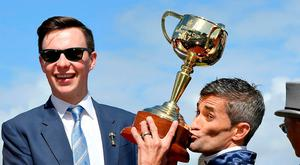 Trainer Joseph O'Brien looks jubilant as Jockey Corey Brown, right, kisses the winning trophy Photo: Andy Brownbill/AP Photo