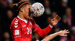 Denmark's Yussuf Poulsen gets a ball in the face while challenging Stephen Ward. Photo: Sportsfile