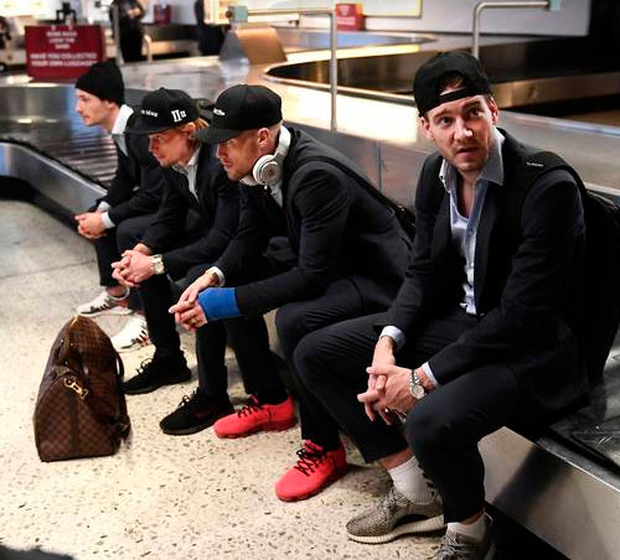 Nicklas Bendtner sits with his team-mates on a luggage carousel at Dublin Airport as the Danish squad were delayed on arrival for tomorrow night's World Cup play-off at the Aviva Stadium