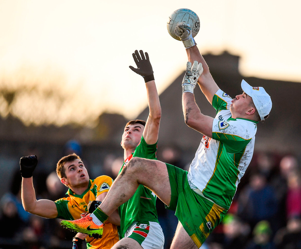 Corofin goalkeeper Bernard Power punches the ball clear of team-mate Liam Silke and Brian Stack of St Brigid's Photo: Brendan Moran/Sportsfile