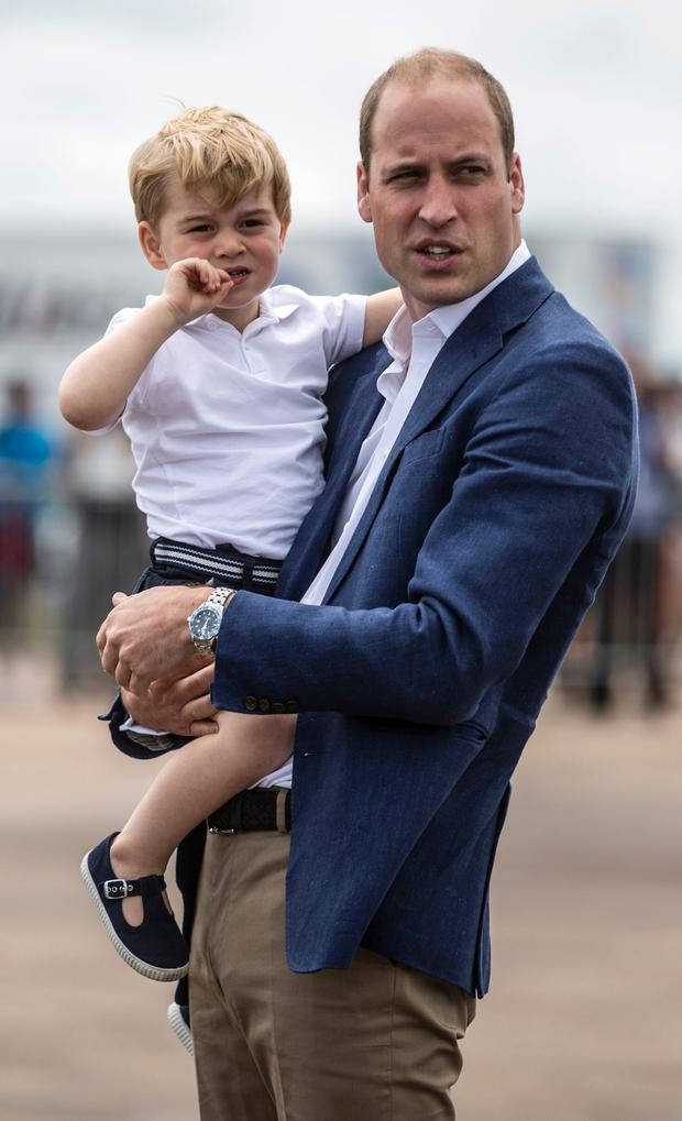 Britain's Prince George is carried by his father Prince William as they visit the Royal International Air Tattoo at RAF Fairford in western England, on July 8, 2016. / AFP / POOL / RICHARD POHLE