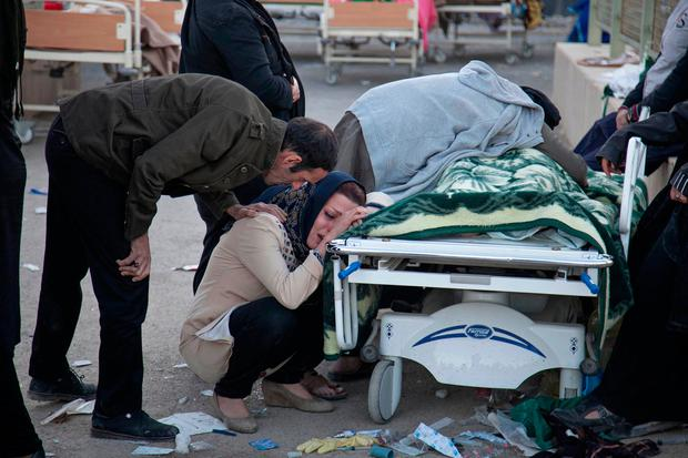 In this photo provided by Tasnim News Agency, relatives weep over the body of an earthquake victim, in Sarpol-e-Zahab, western Iran, Monday, Nov. 13, 2017. (Farzad Menati/Tasnim News Agency via AP)