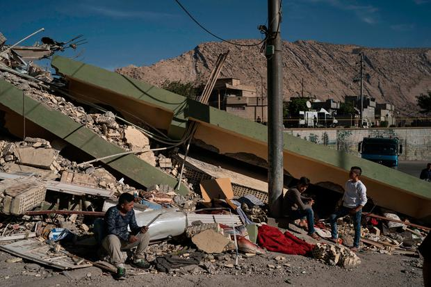 People sit on the rubble of a destroyed house after an earthquake in the city of Darbandikhan, northern Iraq, Monday, Nov. 13, 2017.(AP Photo/Felipe Dana)