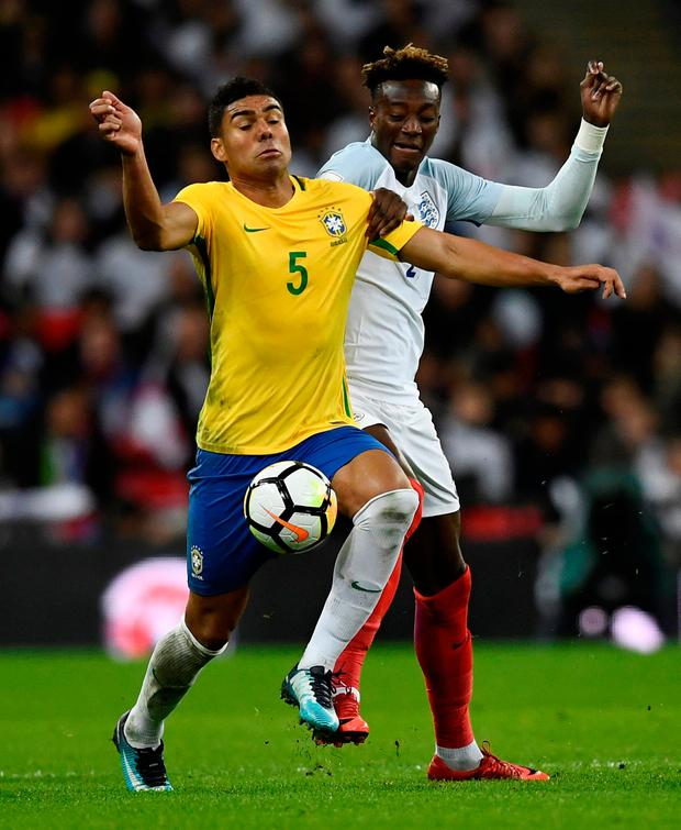 England's Tammy Abraham tussels with Brazil's Casemiro. Photo: Dylan Martinez/Reuters
