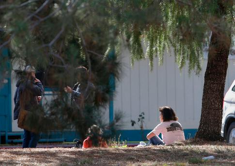 A woman and a child sit by an elementary school where a gunman opened fire in the community of Rancho Tehama Reserve in Corning, California Photo: AP Photo/Rich Pedroncelli