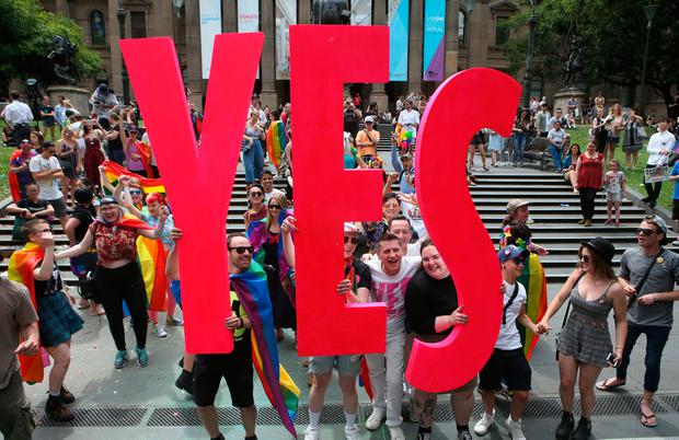 People celebrate after the announcement of the same-sex marriage postal survey result in front of the State Library of Victoria in Melbourne, Australia, Wednesday, Nov. 15, 2017. (David Crosling/AAP Image via AP)