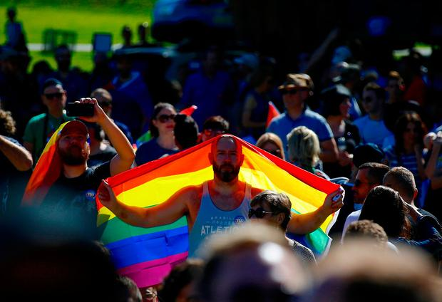 A supporter of the 'Yes' vote holds a colourful flag as he celebrates after it was announced the majority of Australians support same-sex marriage in a national survey, paving the way for legislation to make the country the 26th nation to formalise the unions by the end of the year, at a rally in central Sydney, Australia, November 15, 2017. REUTERS/David Gray