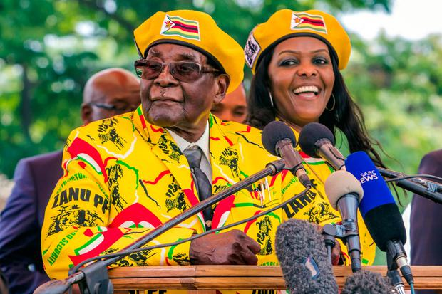 Zimbabwe's President Robert Mugabe (L) addressing party members and supporters gathered at his party headquarters to show support to Grace Mugabe (R) becoming the party's next Vice President after the dismissal of Emerson Mnangagwa. / AFP PHOTO / Jekesai NJIKIZANAJEKESAI NJIKIZANA/AFP/Getty Images