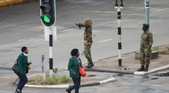 Armed soldiers stand on the road leading to President Robert Mugabe's office in Harare, Zimbabwe Wednesday, Nov. 15, 2017. Overnight, at least three explosions were heard in the capital, Harare, and military vehicles were seen in the streets. On Monday, the army commander had threatened to