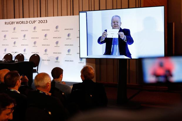 Members of the media watch a live relay as France is named to host the 2023 Rugby World Cup