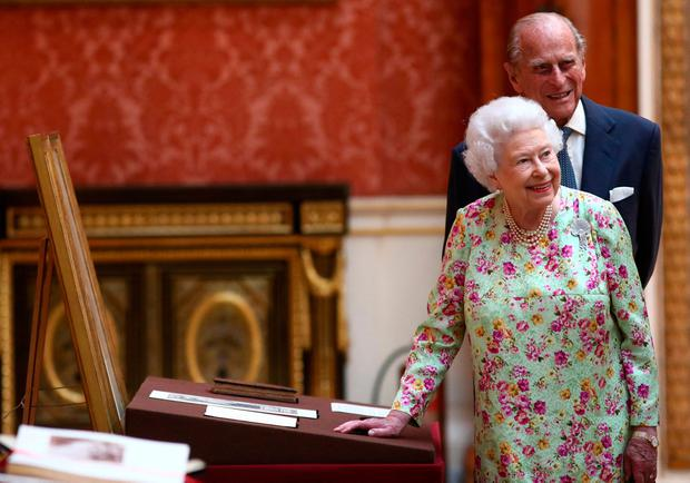 Britain's Queen Elizabeth II and Prince Philip, Duke of Edinburgh stand next to a display of Spanish items from the Royal Collection at Buckingham Palace, London, Britain July 12, 2017. REUTERS/Neil Hall/File Photo