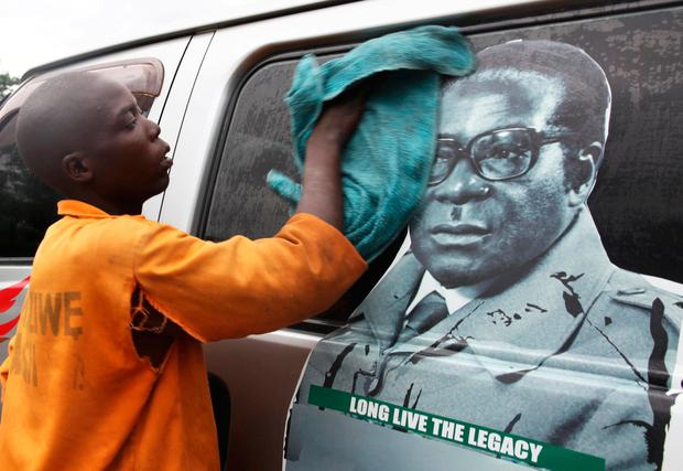 A youth washes a minibus adorned with picture of President Robert Mugabe at a bus terminus in Harare. Photo: Reuters