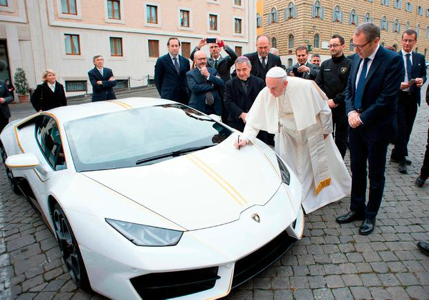 Pope Francis writes on the bonnet of a Lamborghini donated to him by the luxury sports car maker, at the Vatican. The car will be auctioned off by Sotheby's, with the proceeds going to charities. Photo: L'Osservatore Romano/Pool Photo via AP