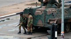 A military tank is seen with armed soldiers on the road leading to President Robert Mugabe's office in Harare, Zimbabwe . Photo: AP