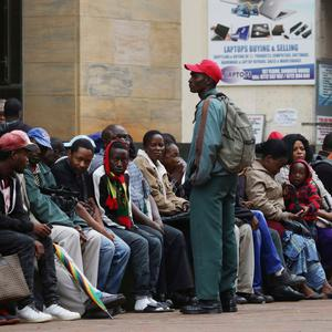 Zimbabweans queue outside a bank to withdraw cash as armed soldiers patrol the streets in Harar on Wednesday