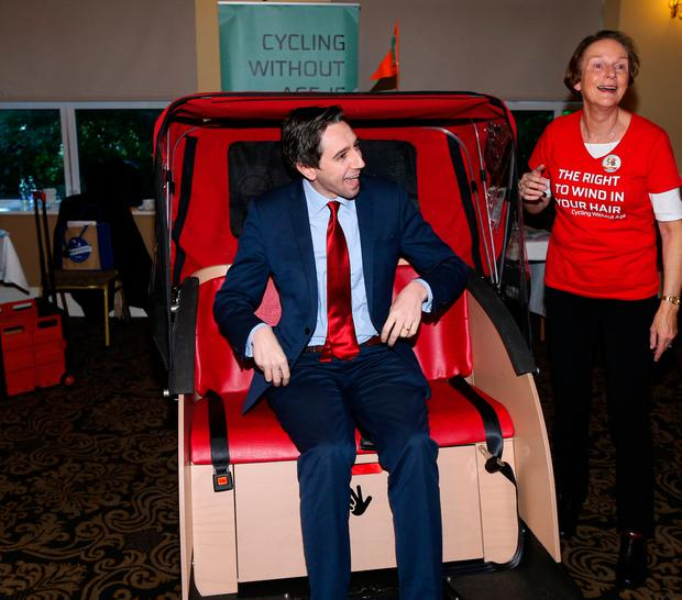Health Minister Simon Harris, pictured with Clara Clark, from Cycling Without Age, gets a ride on a trishaw which takes nursing home residents on outings. It is powered by a cyclist on a push bike behind the chair, which can seat two residents. Nursing home owners were introduced to the transport, part of Cycling Without Age, at the annual meeting of Nursing Homes Ireland. Photo: Maxwells, Dublin