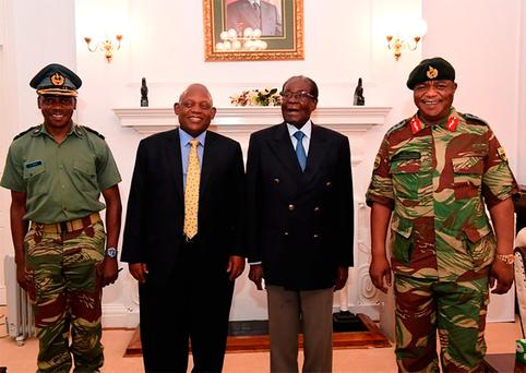 A screengrab from Zimbabwe Broadcasting Corporation (ZBC) yesterday shows Zimbabwe President Robert Mugabe (2R) as he poses alongside Defence Forces Commander General Constantino Chiwenga (R) and South African envoys at State House in Harare. Photo: AFP/Getty