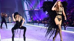 US singer Lady Gaga (L) performs while US model Gigi Hadid presents a creation during the 2016 Victoria's Secret Fashion Show at the Grand Palais in Paris on November 30, 2016. / AFP / Martin BUREAU /