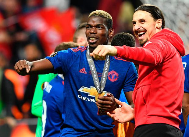 Manchester United's French midfielder Paul Pogba celebrates with his medal and Manchester United's Swedish striker Zlatan Ibrahimovic (R) after the UEFA Europa League final football match Ajax Amsterdam v Manchester United on May 24, 2017 at the Friends Arena in Solna outside Stockholm. / AFP PHOTO / Jonathan NACKSTRAND