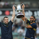 Australian manager Chris Scott, left, and captain Shaun Burgoyne lift Cormac McAnallen Cup as Uachtarán Chumann Lúthchleas Gael Aogán Ó Fearghail looks on after the Virgin Australia International Rules Series 2nd test at the Domain Stadium in Perth, Australia.