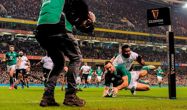 Dave Kearney dives over the line under pressure from Fiji's Timoci Nagusa to score Ireland's second try. Photo: SEB DALY/SPORTSFILE