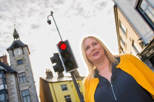 Councillor Melissa Mullane stands under one of Mallow's surveillance cameras Photo: Michael Mac Sweeney/Provision