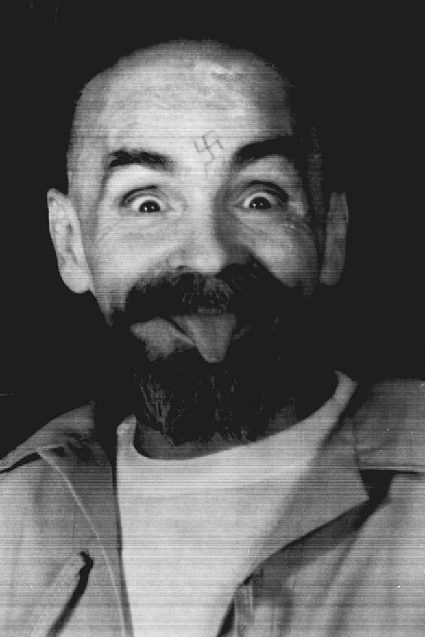 Charles Manson clowns around as he is led to his cell upon the conclusion of his exclusive interview with Reuters August 25, 1989. REUTERS/File Photo