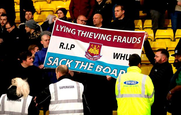 West Ham United fans hold up a banner reading 'Lying Thieving Frauds - R.I.P WHU - Sack The Board'
