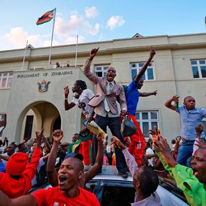 Zimbabweans celebrate outside the parliament building immediately after hearing the news that President Robert Mugabe had resigned (AP Photo/Ben Curtis)