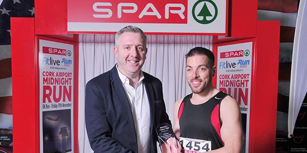 Colin Donnelly, Spar Sales Director presents the 1st Place Men's Trophy to Kevin O'Leary from Mogeely at the Cork Airport 5km Runway Run. Pic Daragh Mc Sweeney/Provision.