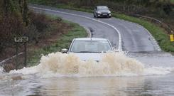 A motorist braves flood waters on the R352 Ennis to Scarriff Road in Co Clare Photo: Press 22